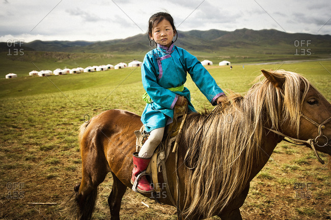 Mongolia - July 17, 2013: Young girl riding a horse in Mongolia
