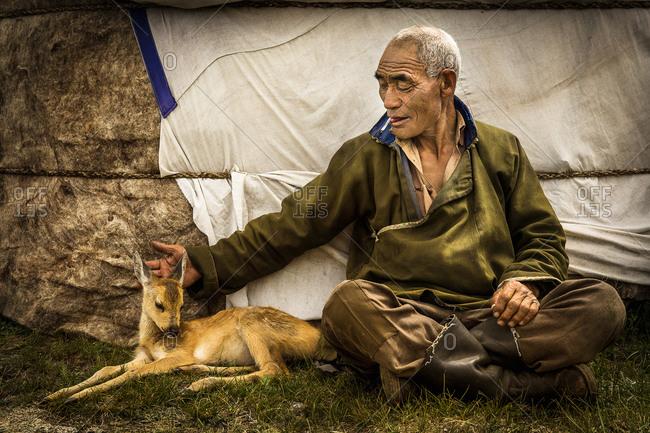 Mongolia - July 22, 2013: Mongolian man with a little fawn