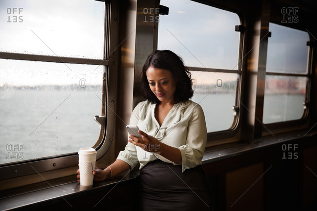 Businesswoman checking her smartphone on the ferry