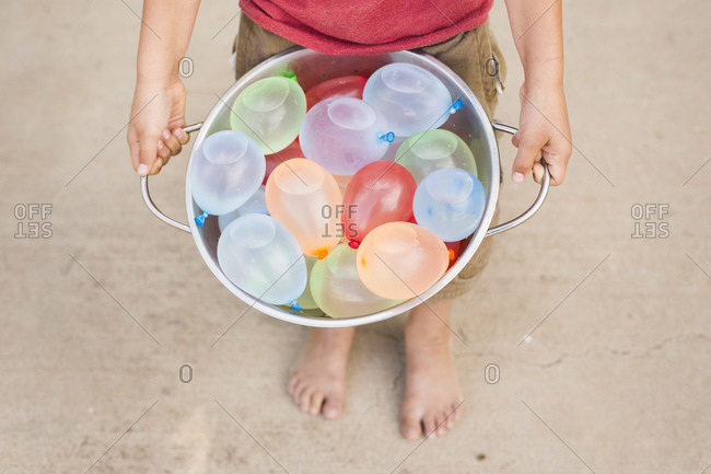 Boy holding a bowl filled with water balloon bombs