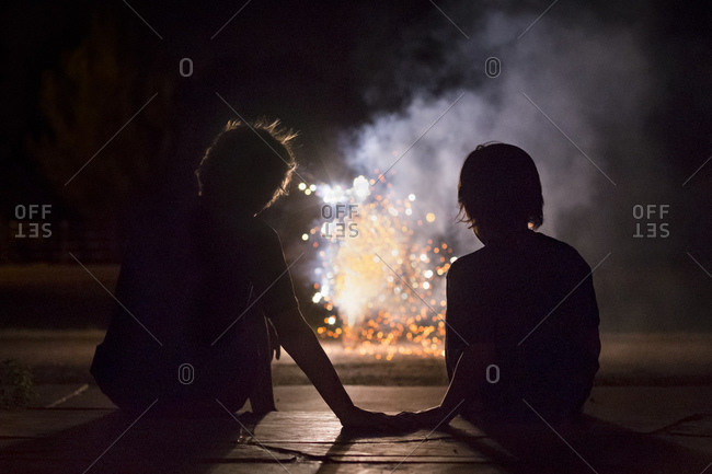Silhouette of boy staring fireworks at 4th of July