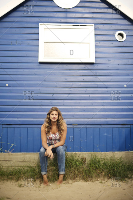 Young woman sitting in front of a blue a beach house