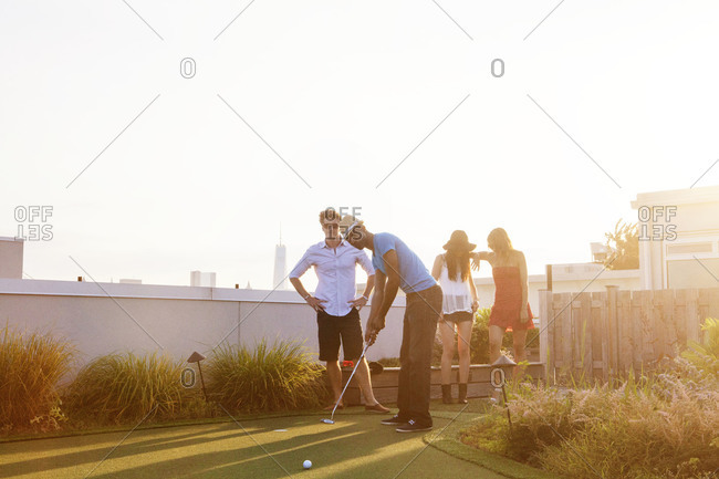 Friends playing miniature golf on rooftop