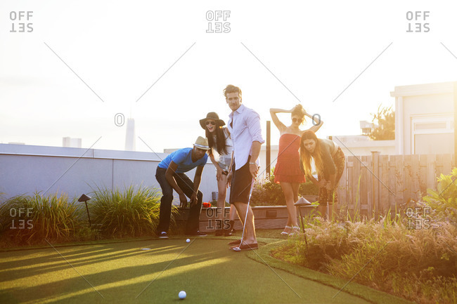 Friends playing miniature golf on urban rooftop