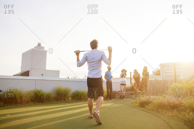 Rear view of man walking with a golf club on rooftop