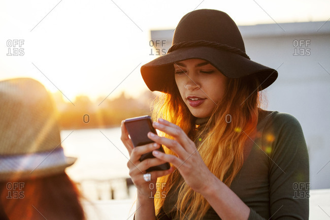 Woman in wide brimmed hat checking her emails on phone
