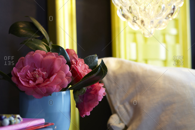 Detail of yellow headboard and pink peonies in vase