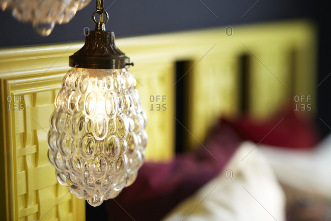 Detail of yellow headboard and lamps in bedroom