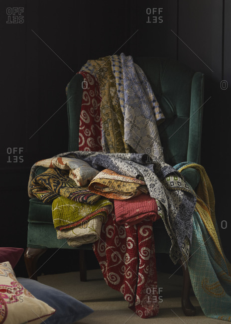 Still life of different quilts arranged on green armchair