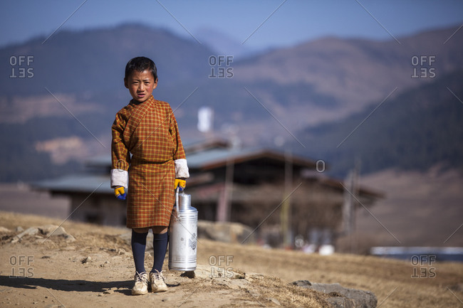Phobjikha Valley, Bhutan - February 7, 2011: Young boy carrying a thermos on a road in the Phobjikha Valley, Bhutan