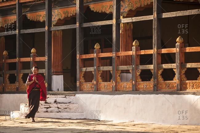 Paro Dzong, Bhutan - February 9, 2011: Monk praying in a courtyard at the Paro Dzong, Bhutan