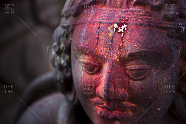 Vermillion and rice offering on the forehead of a statue at the Changu Narayan temple in Nepal
