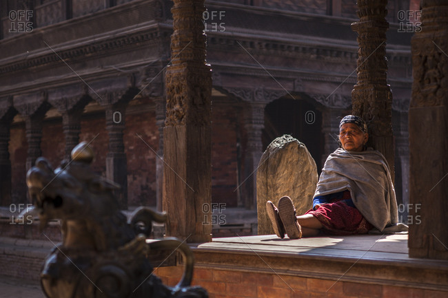 Bhaktapur, Nepal - February 11, 2011: Elderly woman sitting at the Durbar Square in Bhaktapur, Nepal