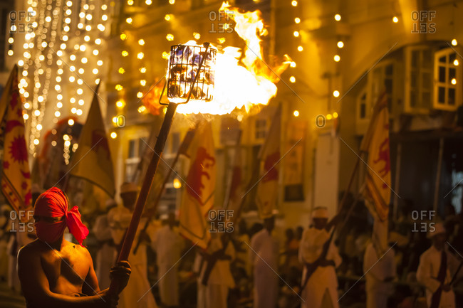 A man holding a torch filled with burning coals at the Esala Perahera parade, in Kandy, Sri Lanka