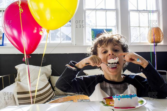 Boy eating a slice of birthday cake