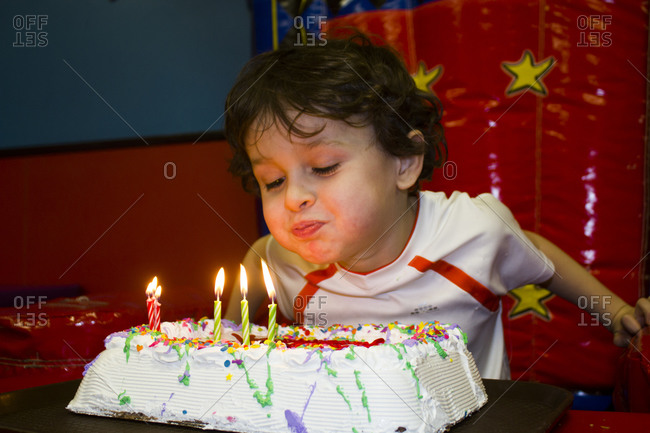 Boy blowing out the candles on his birthday cake