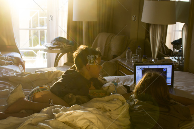 Relaxed kids watching computer in the bedroom
