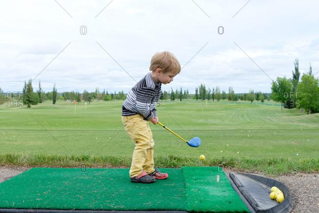 Young boy playing minigolf
