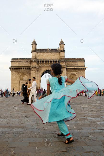 Gateway of India, Mumbai, India - October 3, 2013: Girl dancing at the Gateway of India, Mumbai