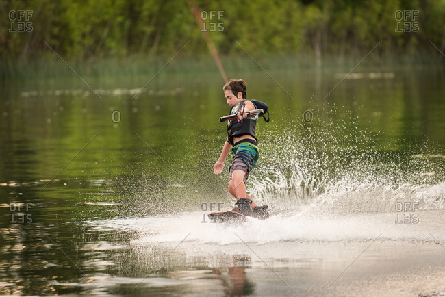 Young boy wakeboarding on a lake