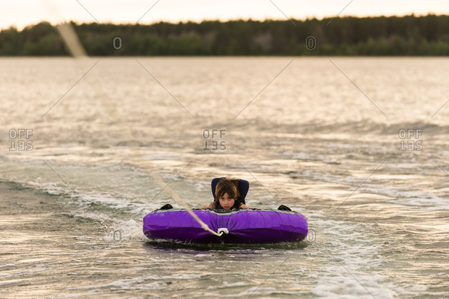 Young boy waterskiing on a towable tube