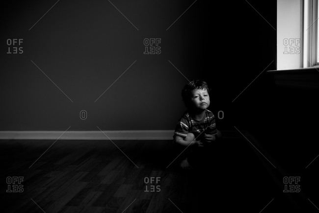 Young boy sitting on the floor