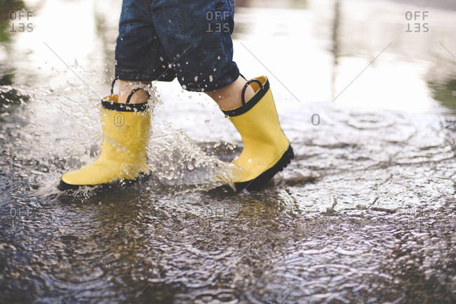 Boy in yellow boots walking in a puddle