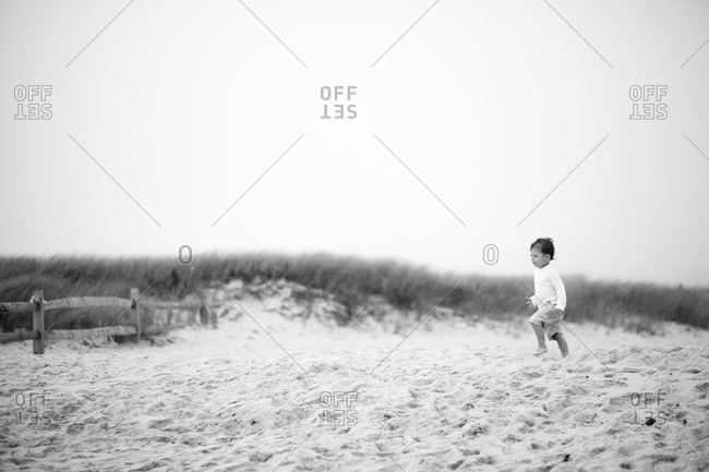 Young boy walking on a beach at Cape Cod