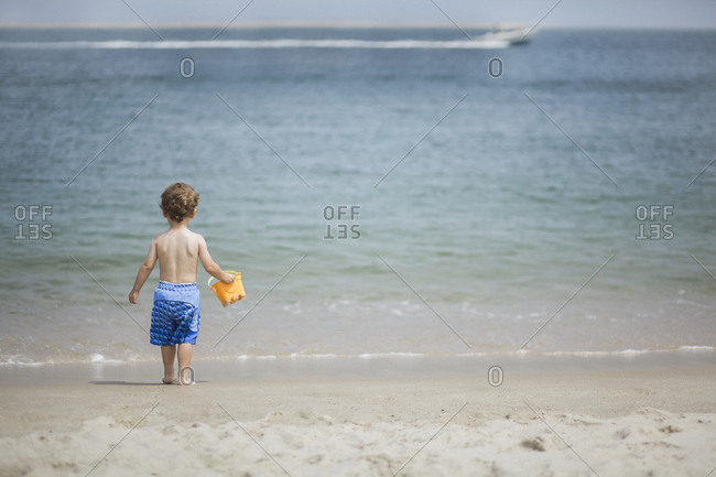 Young boy holding a bucket on a beach at Cape Cod