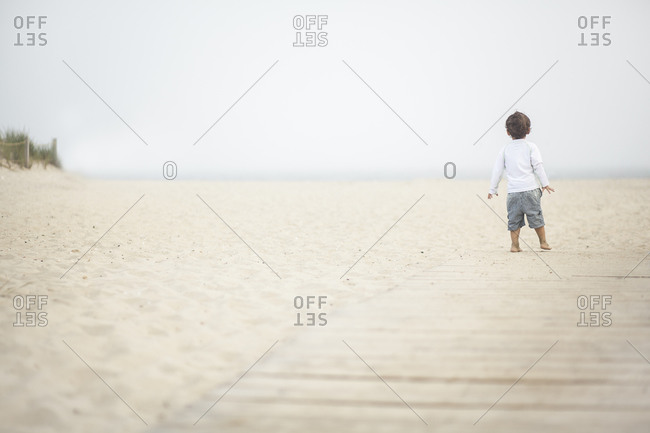 Young boy standing on a foggy beach at Cape Cod