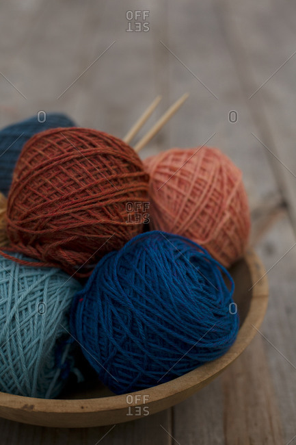 Yarns and knitting needles in a wooden bowl