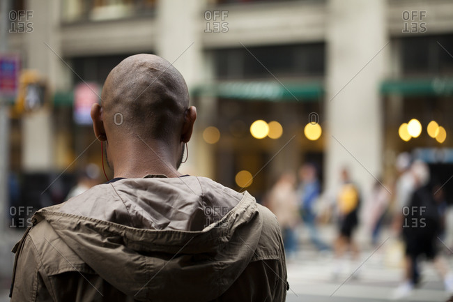 Man listening to music with earphones in New York City, USA