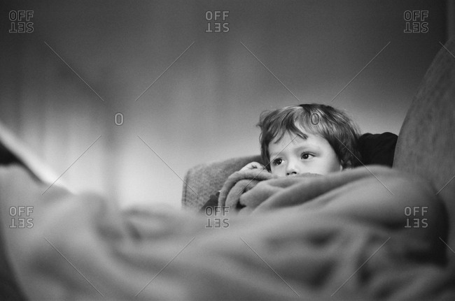 Young boy covered with a blanket