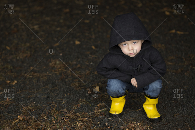 Young boy squatting in yellow rain boots