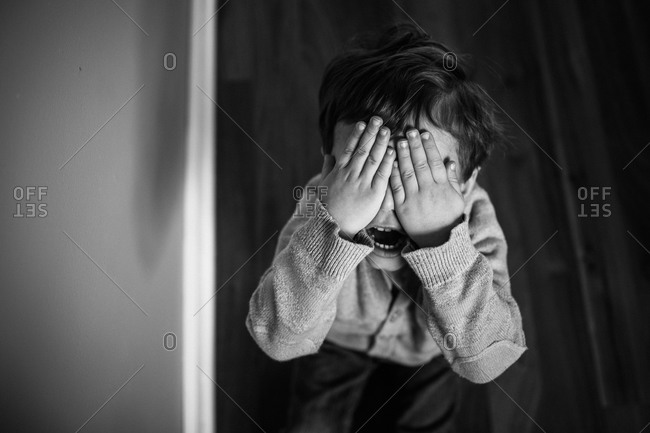 High angle view of boy covering his eyes