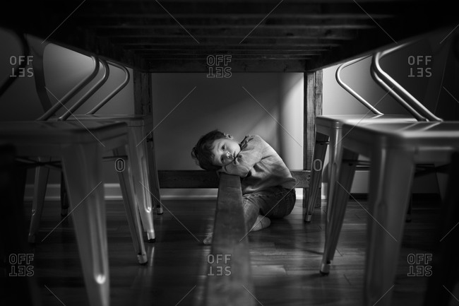 Child sitting under the dining table