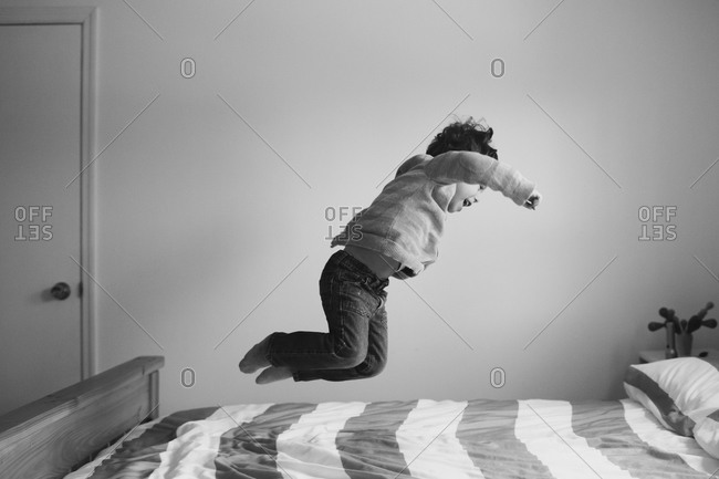 Boy jumping around on a bed