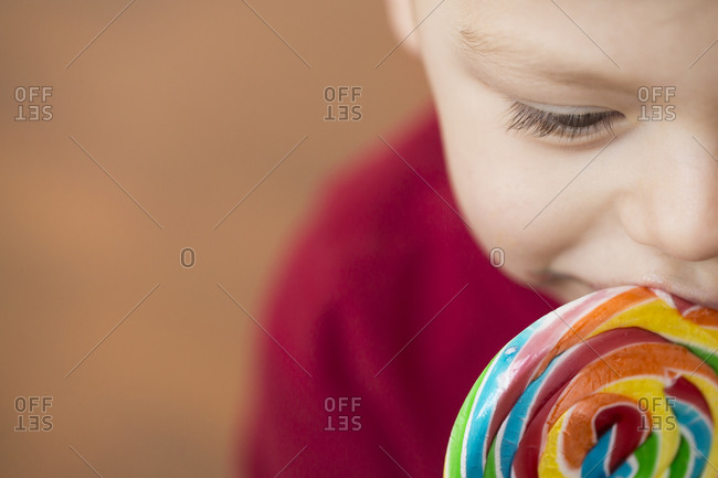 Close up of boy eating a swirl lollipop