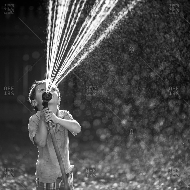 Boy watering the garden with a sprinkler