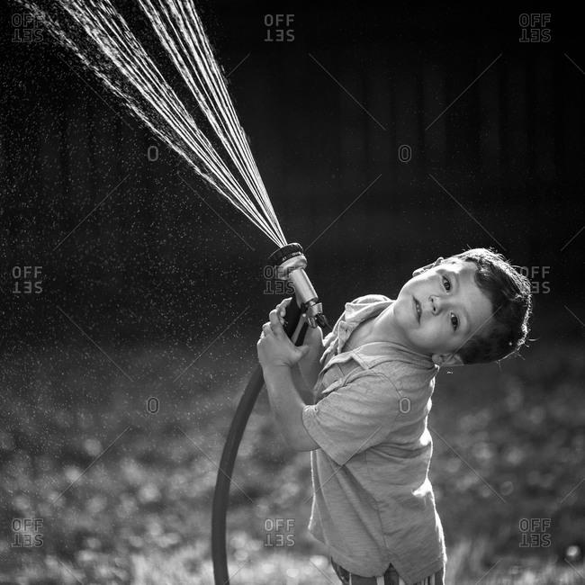 Boy holding a sprinkler in the garden