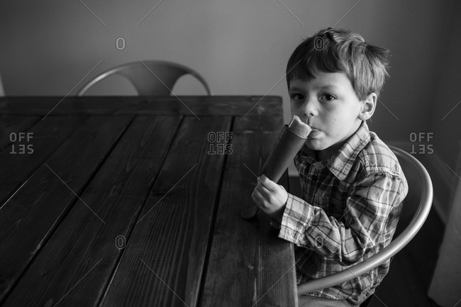 Boy eating an ice pop in the dining room