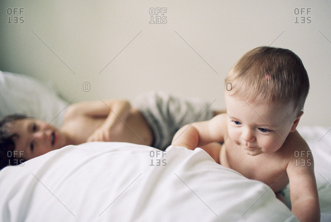 Brothers playing on bed
