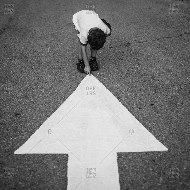 Child pointing on the vertex  of an arrow on asphalt