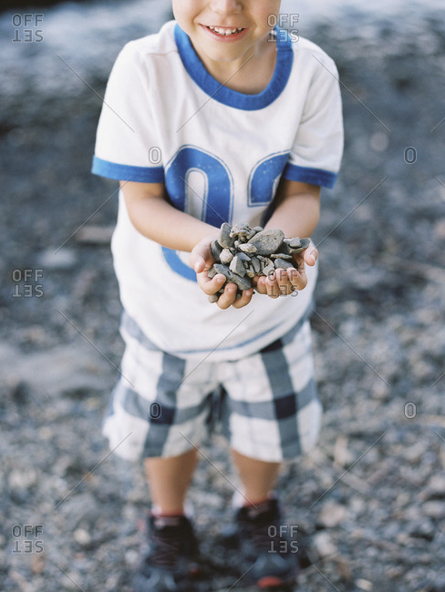 Smiling boy holding a heap of gray pebbles at Donohue Park, Hudson River