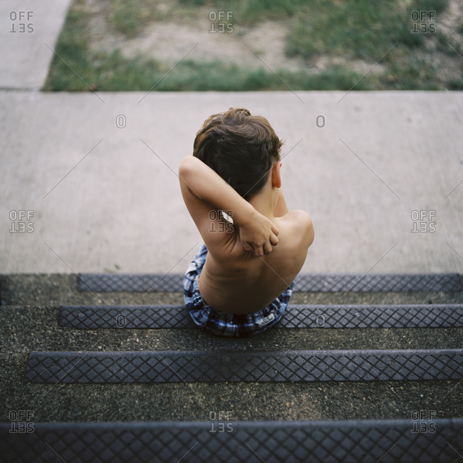 Rear view of boy scratching his own back