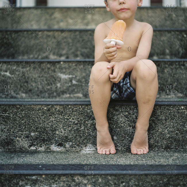 Child eating ice lolly on staircase