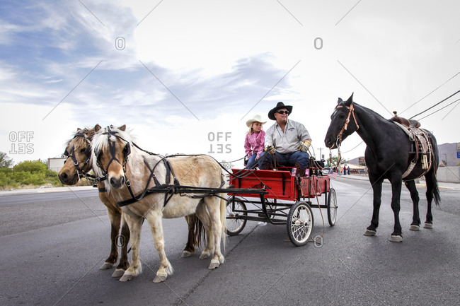 New Mexico, USA - May 11, 2013: Father and daughter riding a horse carriage in Truth or Consequences, New Mexico, USA