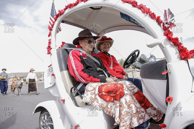New Mexico, USA - May 11, 2013: Elderly couple riding a golf cart at a parade in Truth or Consequences, New Mexico, USA