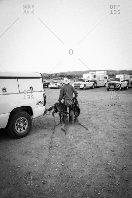 New Mexico, USA - May 11, 2013: Cowboy carries saddle after rodeo in Truth or Consequences, New Mexico, USA