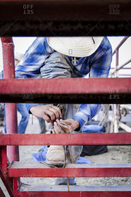 New Mexico, USA - May 11, 2013: Cowboy ties his shoelace in Truth or Consequences, New Mexico, USA